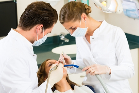 dentista: Paciente de sexo femenino con el dentista y asistente en un tratamiento dental, m�scaras y guantes