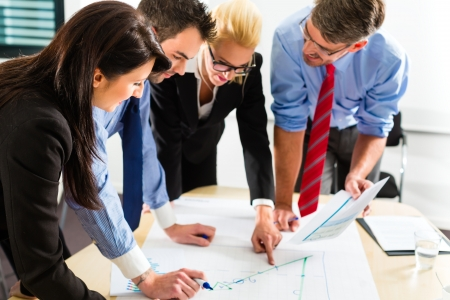 collaboration team: Business - Four professionals in the office in business clothes when planning a strategy for the future of the business