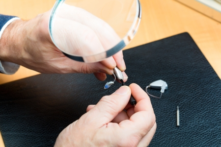 impaired: hearing aid acoustician at work, he is working on a hearing aid for hearing impaired persons Stock Photo