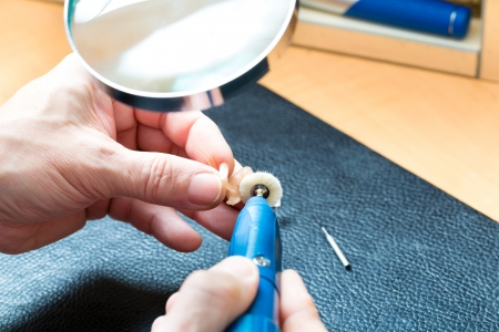 hearing aid acoustician at work, he is working on a hearing aid for hearing impaired persons photo