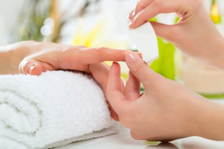 Woman in a nail salon receiving a manicure by a beautician Stock Photo - 18559243