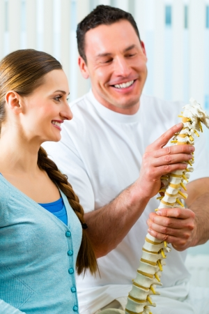 Physiotherapist in his practice, he explains a female patient the vertebral column and the emergence of back pain photo