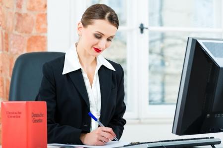 oficinista: Abogado joven que trabaja en su oficina, ella está sentada detrás de las carpetas de escritura en un archivo Foto de archivo