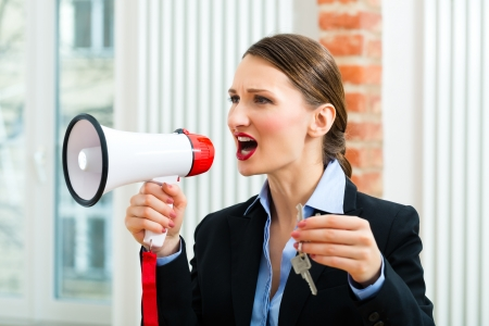 Young realtor is with keys in an apartment, she makes advertising with a megaphone Stock Photo - 18559213