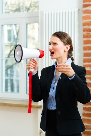 Young realtor is with keys in an apartment, she makes advertising with a megaphone Stock Photo - 18559220