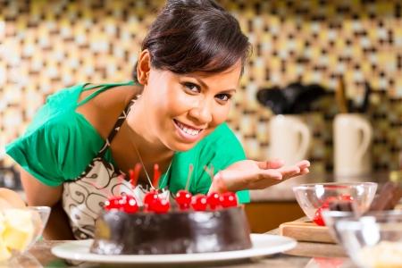 decoracion de pasteles: Mujer asiática que presenta pastel de chocolate hecho en casa con las cerezas se cuece en la cocina de postre