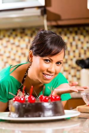 decoracion de pasteles: Mujer asiática que presenta tarta casera de chocolate con cerezas se cuece en la cocina para el postre Foto de archivo
