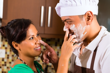 Asian couple in kitchen teasing each other while baking photo