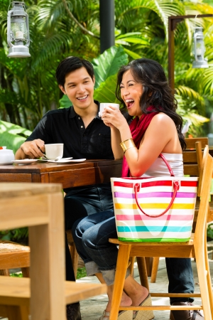 green dates: Asian man and woman in restaurant or cafe having fun drinking hot beverage Stock Photo