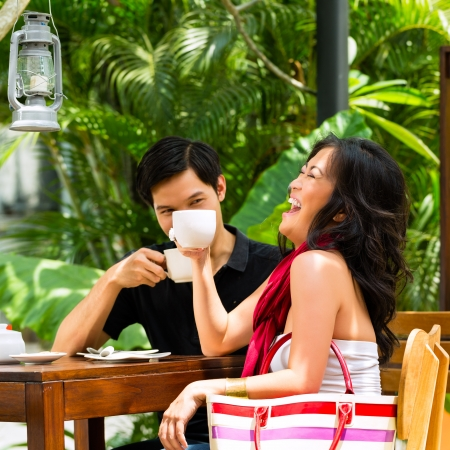 Asian man and woman in restaurant or cafe having fun drinking hot beverage photo