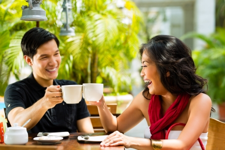 drinking coffee: Asian man and woman in restaurant or cafe having fun drinking hot beverage Stock Photo