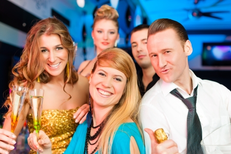 Young people in club or bar drinking champagne and having fun; all are looking into the camera photo