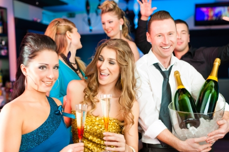 party dress: Young people in club or bar drinking champagne and having fun Stock Photo
