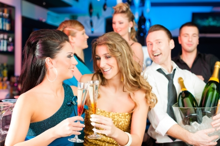 Young people in club or bar drinking champagne and having fun photo