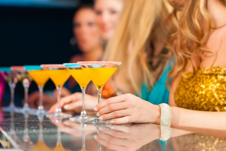 cocktail dress: Young people in club or bar drinking cocktails and having fun; close-up on glasses on the bar Stock Photo