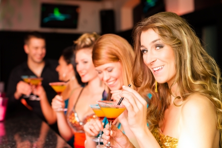 Young people in club or bar drinking cocktails and having fun photo