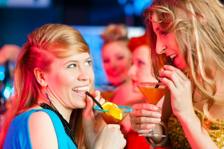 Young women in club or bar drinking cocktails and having fun photo