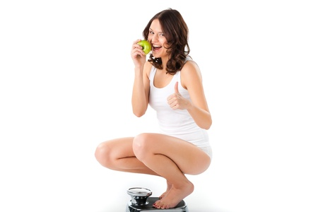 Diet and weight, young woman sitting on her haunches on a scale, she is happy about the success photo