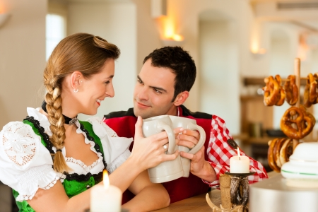steins: Young couple in traditional Bavarian Tracht in restaurant or pub with pretzel and beer