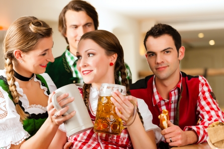clique: Young people in traditional Bavarian Tracht in restaurant or pub with beer and steins