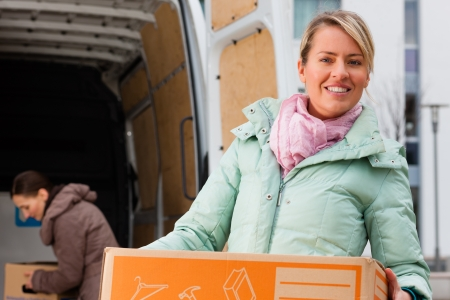 Two young women loading into a moving truck, they carry moving boxes photo