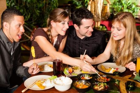Jongeren eten in een Thais restaurant, ze eten met stokjes