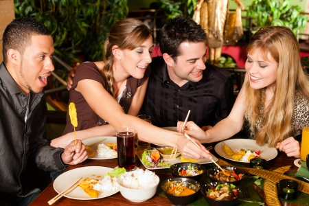 pareja comiendo: Los jóvenes que comen en un restaurante tailandés, que comer con palillos