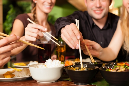Young people eating in a Thai restaurant, they eating with chopsticks Stock Photo - 18687139