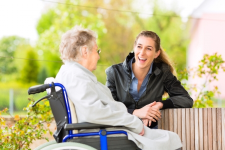 sillas de ruedas: Mujer joven visita a su abuela en el asilo de ancianos Foto de archivo