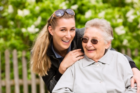 retirement home: Young woman is visiting her grandmother in nursing home having a walk with here in a wheelchair