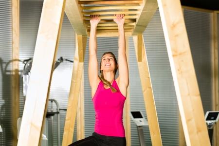 rekstok: Vrouw is opknoping op hoge bar of horizontale balk en opleiden van haar armen Stockfoto