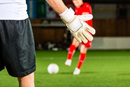 scoring: Man scoring a goal at indoor football or indoor soccer Stock Photo