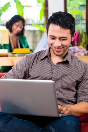 freiberufler: Freelancer - Modedesigner arbeitet zu Hause auf einem Design oder Entwurf, ihr Freund sitzt mit einem Laptop auf der Couch