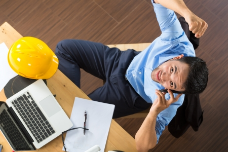 Freelancer - Architect working at home on a design or draft, on his desk are books, a laptop and a helmet or hard hat Stock Photo - 18687407