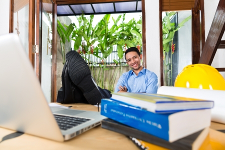 telecommuter: Freelancer - Architect working at home on a design or draft, on his desk are books, a laptop and a helmet or hard hat Stock Photo