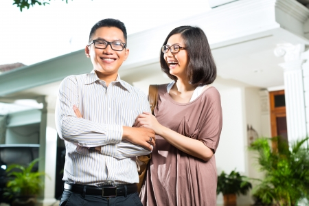 homeowner: Indonesian couple in tropical environment in front of a your superior house, he embraces his wife Stock Photo