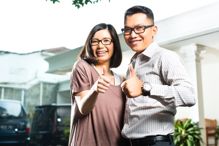Indonesian couple in tropical environment in front of a your superior house, he embraces his wife photo