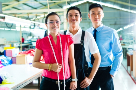 textile designer: Shift supervisor or foreman, together with the owner or CEO and the designer, look at a draft for the new collection, they standing in a textile factory