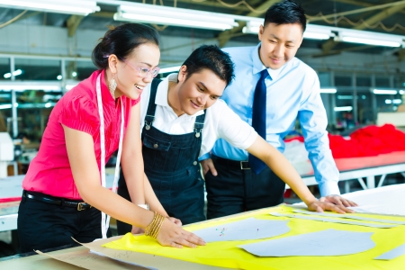 Female Designer or a seamstress, sewer, worker or production manager and owner or CEO look at pattern on a table in a textile factory Stock Photo