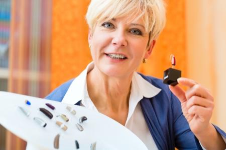 personas escuchando: Una m�s vieja mujer jubilada o con problemas de audici�n hacer una prueba de audici�n y pueden necesitar un aud�fono, ella busca en una selecci�n de los