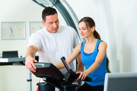 back injury: Patient at the physiotherapy making physical exercises with her therapist Stock Photo