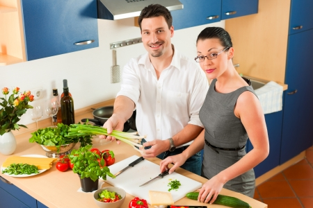 Man and woman in the kitchen - they preparing the vegetables and salad for dinner or lunch Stock Photo - 18908714