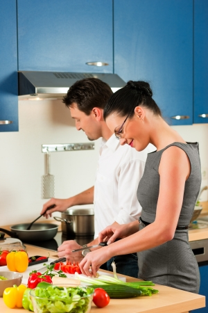 Man and woman in the kitchen - they preparing the vegetables and salad for dinner or lunch Stock Photo - 18908807