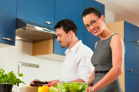 Man and woman in the kitchen - they preparing the vegetables and salad for dinner or lunch Stock Photo - 18908753