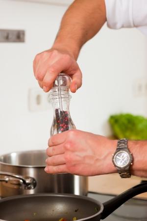 Mann in der Küche - nur die Hände zu sehen - ist das Hinzufügen von Gewürzen auf Nahrung