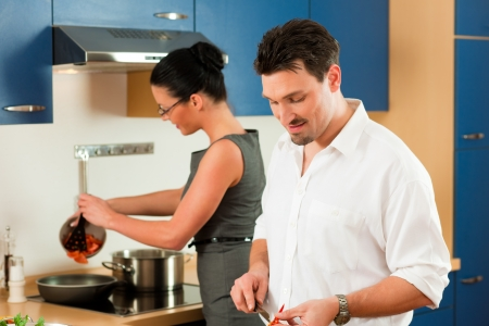Man and woman in the kitchen - they preparing the vegetables and salad for dinner or lunch Stock Photo - 18908704