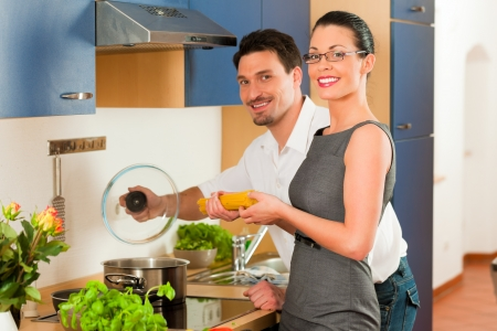 Man and woman in the kitchen - they preparing the vegetables and salad for dinner or lunch Stock Photo - 18908744