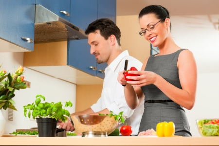 Man and woman in the kitchen - they preparing the vegetables and salad for dinner or lunch Stock Photo - 18908716
