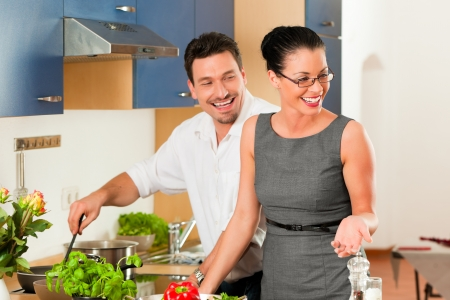 Man and woman in the kitchen - they preparing the vegetables and salad for dinner or lunch Stock Photo - 18908728