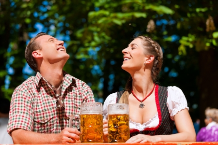 tracht: Happy Couple sitting in Bavarian Beer garden and enjoy the beer and the sun Stock Photo